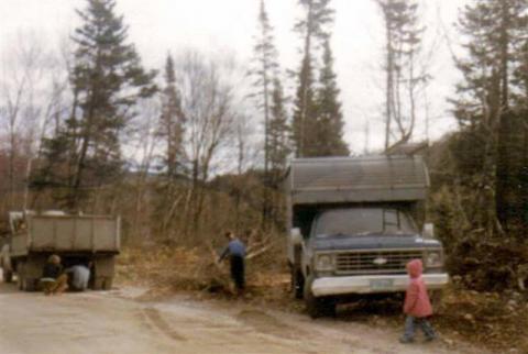 Avec son camion chevrolet 75, au chalet en train de bûcher du bois, avec la petite Isabelle.